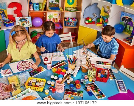 Small students painting in art school class. Children boy and girl drawing by paints on table. Portrait of kids in kindergarten. Preparing for a children's art exhibition.