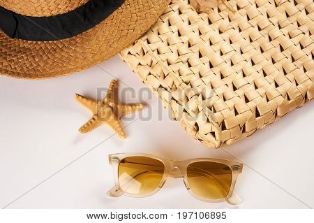 Summer vacation essentials on a white background. Straw hat sunglasses seashell and straw beach bag isolated on white background with copy space.