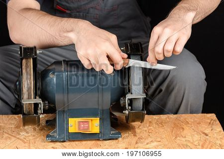 A man in working clothes hones professional sharpening kitchen knive on the table more horizontal knife