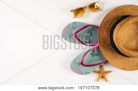 Summer beach women's accessories straw hat sun glasses shoes and sea star isolated on white background with copy space. Summer holiday background. Top view