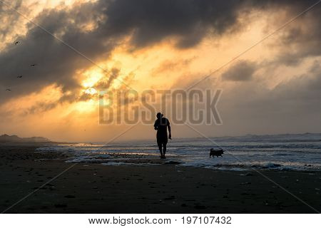 Silhouette man walking dog in the morning sunrise at Folly Beach, South Carolina