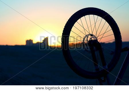 the silhouette of the bike wheel at sunset