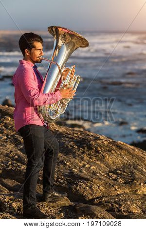 Tuba - instrument. Young man play the trumpet on rocky sea coast during surf.