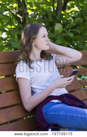 A young girl with a phone on a bench in jeans a T-shirt and a checkered red shirt tied on her belt looks forward to the side