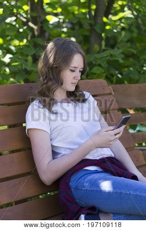 Young girl with a phone on a bench in jeans a T-shirt and a checkered red shirt tied on her belt reads a message on the smartphone