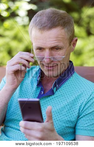 Middle-aged man wearing glasses on the nose close-up with a surprise reading a message on a smartphone sitting on a bench in a city park