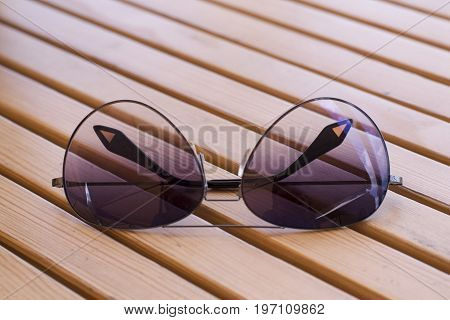 Sunglasses on wooden decorations of light brown color