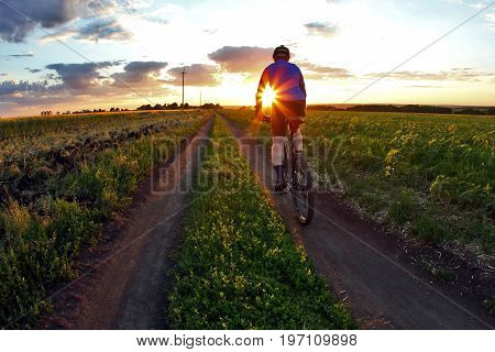 cyclist rides a bicycle on a track at sunset