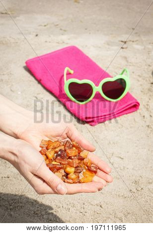 Amber Stones In Hand And Accessories For Vacation At Beach