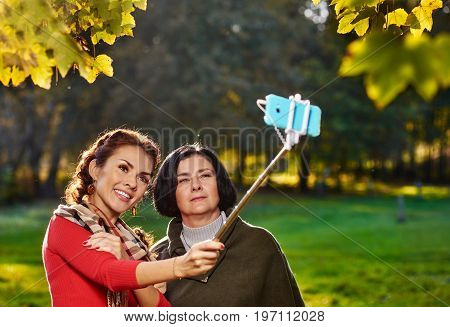 Smiling cheerful family making selfie with monopod in park