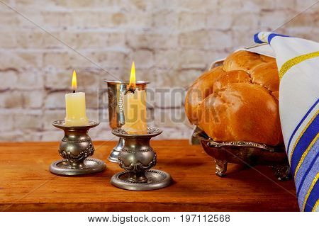 Shabbat Candles In Glass Candlesticks With Blurred Covered Challah