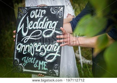 Anniversary wedding celebration is outdoor. hanging black board