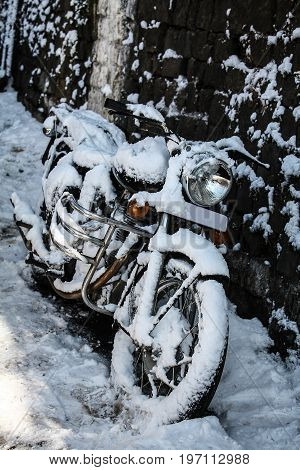 A snowbound motorcycle stands at the edge of a walkway / Snowbound motorcycle