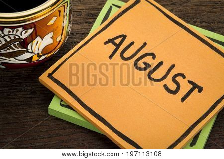 August - handwriting in black ink on a  sticky note with a cup of coffee