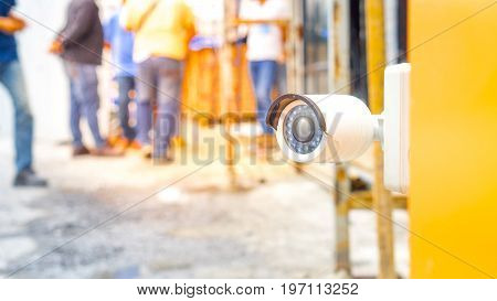 Surveillance video camera and security concept - Close up Surveillance cctv video camera on gate of construction site people with flare light effect and copyspace