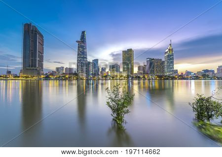 Ho Chi Minh City, Vietnam - June 15th, 2017: Riverside City sunrays clouds in the sky at end of day brighter coal sparkling skyscrapers along beautiful river in Ho Chi Minh City, Vietnam