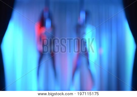 Two sexy strippers blur effect without focus - can be used as blurred background
