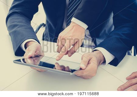 Two businessmen using tablet computer with one hand touching the screen business discussion concept - vintage style effect