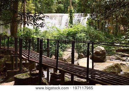Steel Bridge With Sridith Waterfall In Tropical Rain Forest
