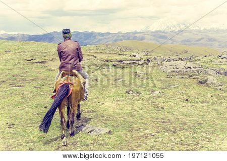 View on tibetan man on a horse in tibetan highlands in China