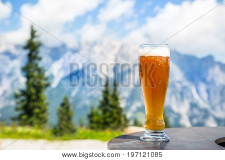 Beer. Cold golden draft beer in glass over alps. Tasty beer and tourist season in the mountains or the Alps.
