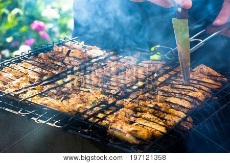 Delicious juicy pieces of pork on the grill are checked with a knife while cooking