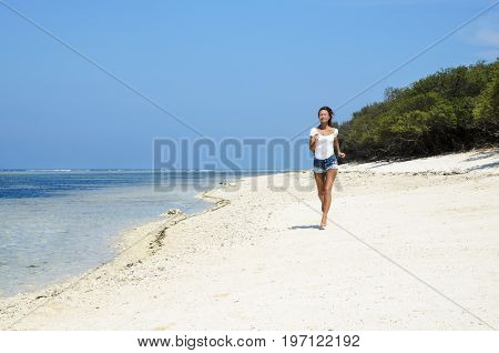 Active sporty woman run along ocean surf by water pool. Sunset sand beach background with blue sky and sun. Woman fitness, jogging workout and sport activity on summer holiday.