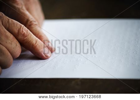 Closeup of hands touching reading braille letters