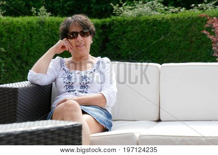 portrait of smiling middle age woman with sun glasses sitting in garden at home