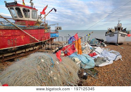 HASTINGS, UK - JULY 21, 2017: Beach launched fishing boats with colorful fishing nets in the foreground