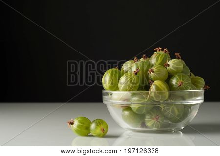 Juicy ripe berries of a gooseberry in a small glass plate on black surface. Gooseberry harvest.