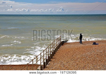 HASTINGS, UK - JULY 23, 2017: A fisherman on the beach of Hastings with a blue sky with nice clouds