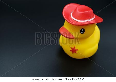 a squishy bright yellow plastic model duck on black background