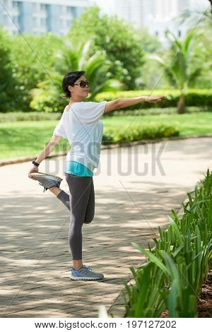 Portrait of cheerful Asian woman warming up and stretching legs during jogging workout in park on sunny day