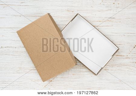Open cardboard box with cover on wooden table above view