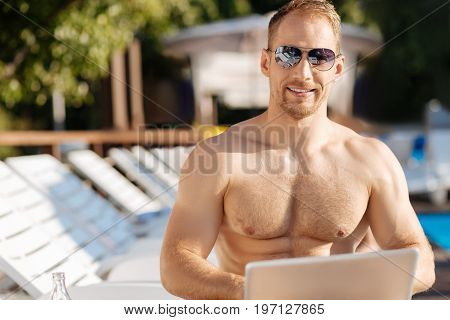 Pleasant summertime. Cheerful sturdy young man in sunglasses sitting on a chaise longue near the swimming pool, working on the laptop and smiling at the camera