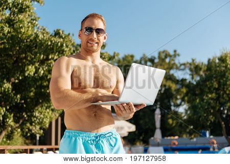 Pleasant working ambience. Fit young man in sunglasses in the middle of a private beach and holding a working laptop while smiling at the camera