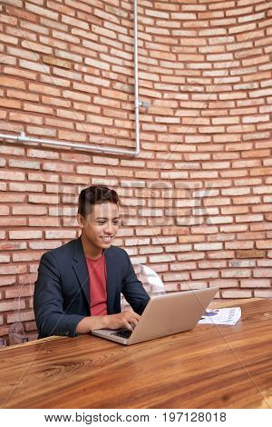 Portrait of smiling Asian man using laptop sitting against brick wall and working
