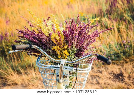 Bicycle with a bouquet of wildflowers in a basket in front of handlebar on a background of green grass in wheat field