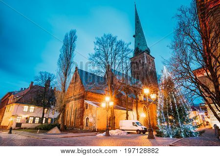 Riga, Latvia. Cathedral Basilica Of St. James, Pyramidal Monument To Barricades And Perished People On January 20, 1991 And Holiday Xmas Christmas Tree At Evening Or Night Illuminations. UNESCO