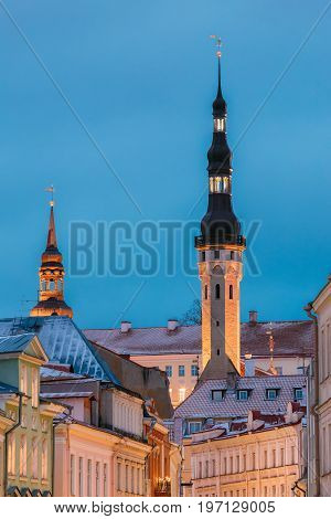 Tallinn, Estonia, Europe. Old Medieval Tower Of City Hall On Blue Sky Background. Ancient Tower Of Town Hall In Evening Or Night Illuminations. Historic Centre Old Town. UNESCO World Heritage Site