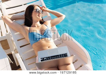 Day of relax. Pleasant upbeat curvy woman sunbathing on a chaise longue near a swimming pool, looking into the distance while holding a laptop in her lap