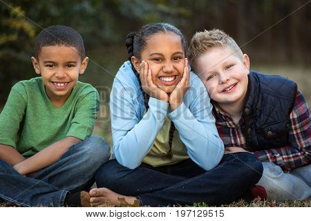 Happy diverse group of kids outside at a park.