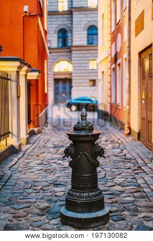 Riga, Latvia. Small Column Pillar Shaft Stake Pile With Lions Heads At Torna Street In Old Town. Narrow Street In Evening Or Night Illuminations Light.