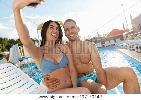 Goofing around. Joyful young couple sitting on a chaise longue near a swimming pool and taking funny selfies while the woman showing her tongue and the man hugging her