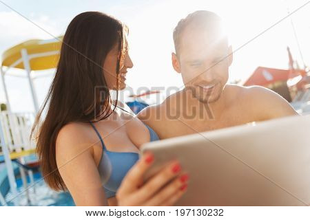 Check this out. Beautiful brunette woman showing a video on her laptop to her charming boyfriend while watching him react to it