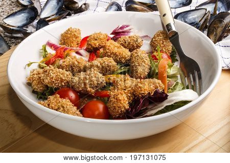breaded mussels with fresh salad in a white deep plate