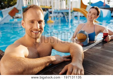 Chilling together. The focus being on an upbeat young man resting his elbows on a swimming pool side while his wife wearing a bird-shaped swim ring and holding a soda in the background