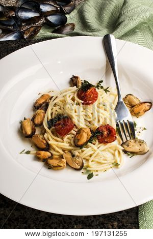 spaghetti with grilled tomatoes thyme and mussels on a white plate