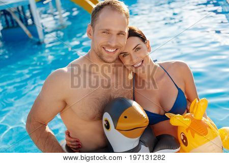 Best honeymoon. Beautiful loving young couple standing in the swimming pool, wearing animal-shaped swim rings and smiling at the camera cheerfully